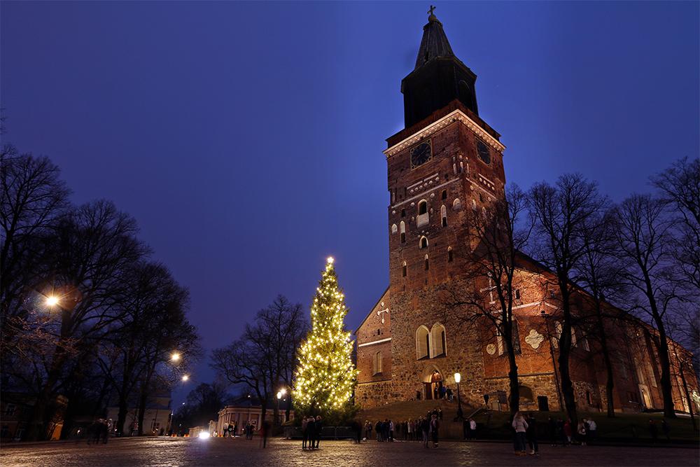 Valokuvassa Turun tuomiokirkko kuvattuna ulkoapäin tuomiokirkontorilta edessään sähkökynttilöin koristettu joulukuusi.