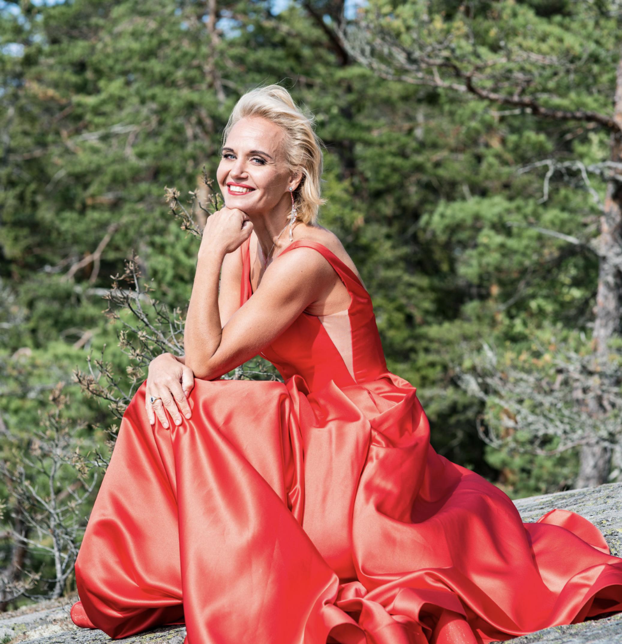 Cecilia von Hartman poseeraa punaisessa iltapuvussa luonnon keskellä