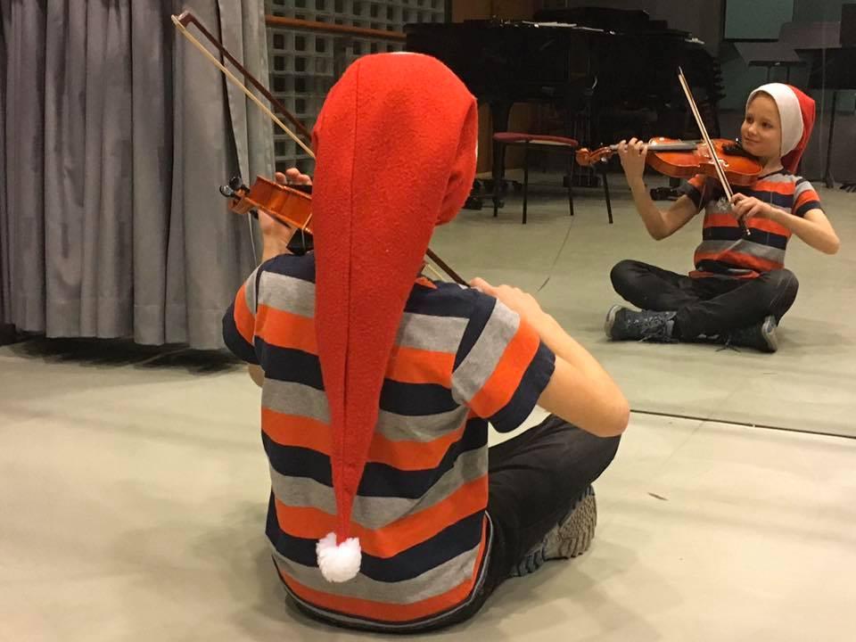 Tonttulakkiin pukeutunut lapsi soittaa viulua peilin edessä