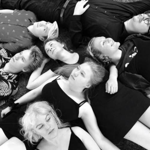Turun konservatorion ja musiikkiopiston opiskelijoita; mainoskuvassa seitsemän hymyilevää nuorta makaa lattialla.