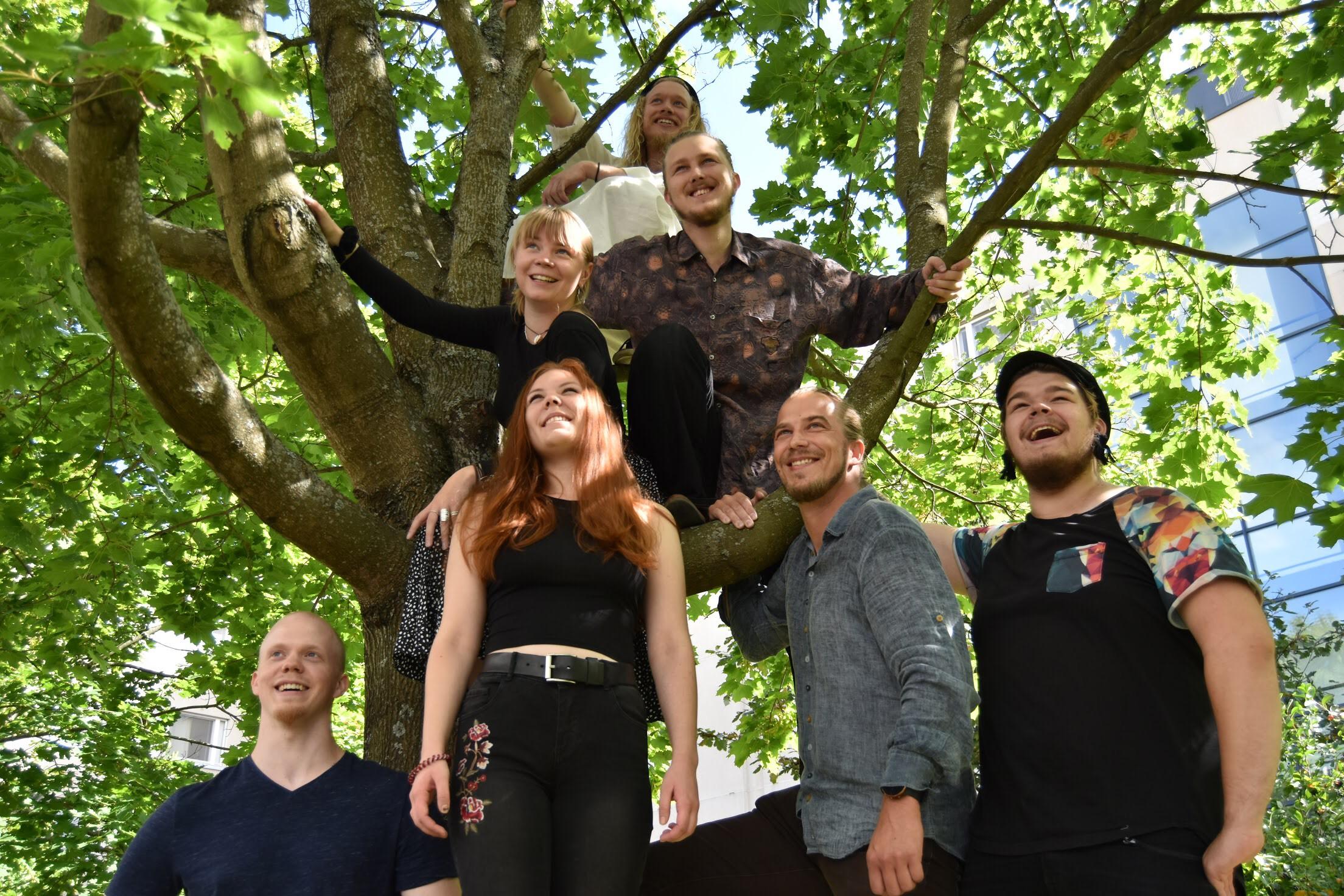 Salmon snake yhtye valokuvassa. Seitsemän hymyilevää nuorta aikuista vaahterassa.