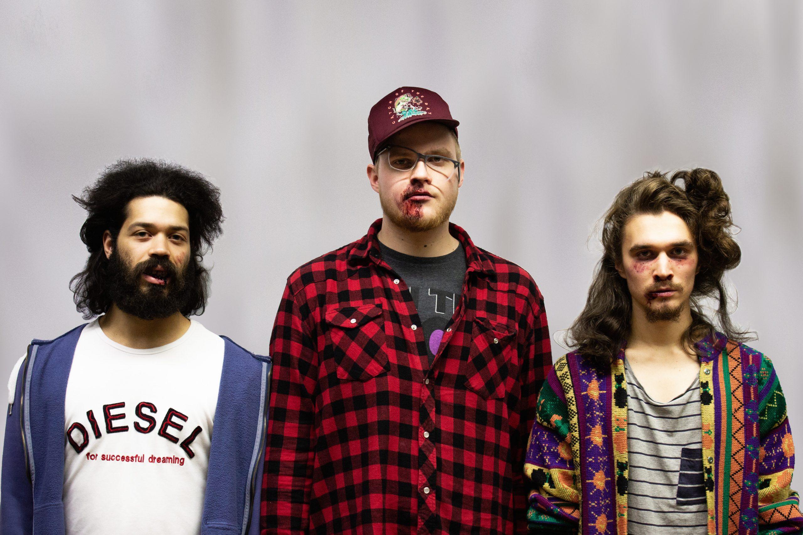Nujakka-yhtyeen promokuvassa kolme nuorta lievästi pahoinpideltyä nuorta miestä.